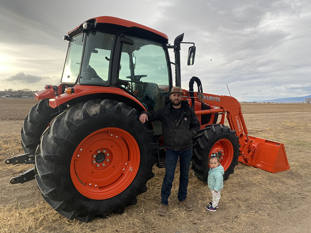 Dustin with his daughter in front of tractor